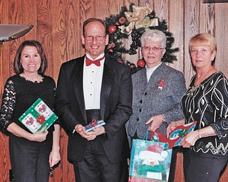 The Youngstown Area Federation of Women's Clubs had its annual Christmas party at Tippecanoe Country Club with music provided by Jack Ciarniello, followed by a drawing for special holiday prizes. Members took books for the children at Beatitude House. From left are Debra Kostelic, president; Ciarniello; Sally Schlabaugh, treasurer; and Rusti Puromaki, first vice president.