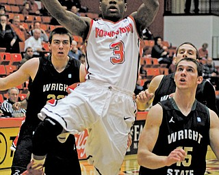 Youngstown State's Kendrick Perry (3) goes up for a layup around Wright State defenders Kendall Griffin (15) during Wednesday's Horizon League game at YSU's Beeghly Center. Perry had his first double-double of the season with 14 points and 10 rebounds as the Penguins downed the Raiders, 68-61.