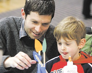 "Shlomo Jacobs-Velde, 4, concentrates on putting foam and paper pieces together to make a floral centerpiece during a program related to Tu B'Shevat, the ""new year"" for trees in the Jewish tradition. Shlomo and his father, Rabbi Josh Jacobs-Velde of Congregation Ohev Tzedek in Boardman, attended the program this week at Temple El Emeth in Liberty."