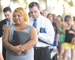In this Jan. 15 photo, Racheel Weston stands in line with a few hundred other job-seekers during a job fair hosted by the Miami Marlins at Marlins Park in Miami. The number of Americans seeking unemployment benefits fell last week to the lowest level in fi ve years, a positive sign that layoff s have fallen and hiring may pick up.