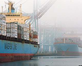 In this Dec. 5, 2012, photo, containers are unloaded from cargo ships at the Port of Los Angeles. The U.S. economy shrank unexpectedly in the October-December quarter of 2012, at an annual rate of 0.1 percent.