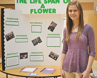 Lexxi Haluska, an eighth-grader at St. Joseph and Immaculate Heart of Mary School, poses in front of her science-fair project. Sixth- and eighth-graders presented their projects Wednesday for multiple judges.