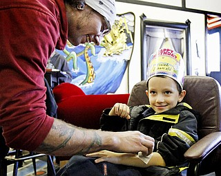 Nick West, another employee at the studio, gives 6-year-old Isaiah Howley a temporary tattoo of a skull on his birthday.