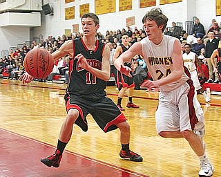 Canfield's Andrew Midgley (11) and Cardinal Mooney's George Brandenstein (24) chase the ball during their basketball game Tuesday at Mooney High School in Youngstown. Canfield edged Mooney, 60-59.