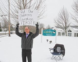 Jim Sobien, an Austintown schools parent, holds up a sign as he conducts a protest of the Austintown school district's job fair that took place at the Austintown branch of the Public Library of Youngstown & Mahoning County on Raccoon Road on Tuesday. Sobien, pointing out that teacher-contract negotiations are ongoing, was the only one conducting the protest when the job fair started.
