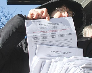 Anti-fracking activist Lynn Anderson holds a stack of petitions that she and others delivered to Youngstown City Hall on Wednesday.