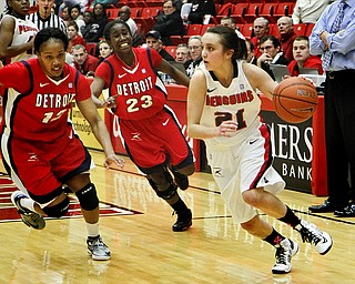 MADELYN P. HASTINGS | THE VINDICATOR  Youngstown's Liz Hornberger (21) dribbles the ball down the court while Detroit's Demeisha Fambro (12) and Senee Shearer (23) try to keep up during the second half of the game at the Beeghly Center on February 7, 2012. The Penguins beat the Titans 58-53.