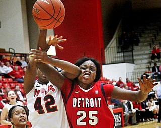 MADELYN P. HASTINGS | THE VINDICATOR  Youngstown's Brandi Brown (42) shoots the ball while Detroit's Demeisha Fambro (12) and Yar Shayok (25) try to block her during the first half of the game at the Beeghly Center on February 7, 2012. The Penguins beat the Titans 58-53.
