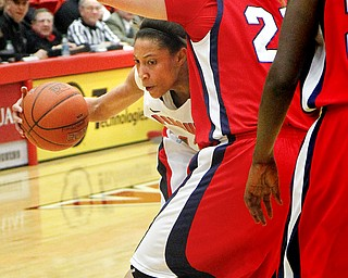 MADELYN P. HASTINGS   THE VINDICATOR  Youngstown's Karen Flagg (14) dribbles the ball down the court while Detroit's Audrey Matteson (21) defends during the first half of the game at the Beeghly Center on February 7, 2012. The Penguins beat the Titans 58-53.