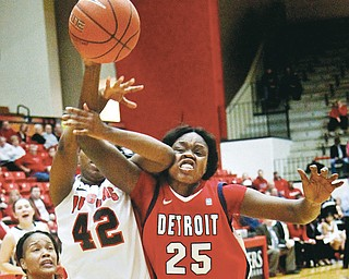 Detroit's Yar Shayok (25) is elbowed in the face by Youngstown State's Brandi Brown (42) as Brown takes a shot during the first half of their game Thursday at YSU's Beeghly Center. The Penguins defeated Titans, 58-53.