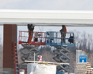 Crew members work on the ceiling of a fueling area at the Ohio Turnpike's Glacier Hills service plaza in New Springfield. That plaza and the Mahoning Valley plaza should reopen before Memorial Day.