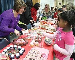 Poland North Elementary second-grader Arikia Chism makes a purchase from Melissa Kellgren, a member of the parent-teacher organization, during a bake sale Tuesday. The event benefited the Diaz family of Poland, whose 7-month-old son, Jackson, was born with a rare congenital disorder.