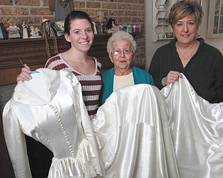 Holding the wedding gown that has been passed down for three generations are Lyndsey Wade, Jean Rabold and Dawna Cramer.