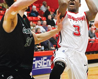 YSU's Kendrick Perry (3) attempts to shoot the ball while Green Bay's Alec Brown (21) tries to block his shot during the second half of Sunday's game at the Beeghly Center. Green Bay beat the Penguins 71-54.