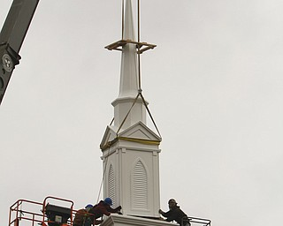The 32-foot spire at Ellsworth Presbyterian Church is put into place above the antique cast-iron bell by crew members of Joseph Sylvester Construction and Mulholland Roofing. The spire and bell tower were damaged by wind in 2009; donations and fundraisers made the new spire and installation possible.