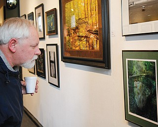"David Richards of Warren looks at photographs in the ""Photo 2013"" exhibit at the Trumbull Art Gallery in Warren."