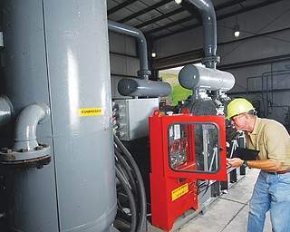A Waste Management technician works inside a plant that converts landfill gas to energy. Rather than wasting the gas by burning it on a flare, the Mahoning Landfill is piping it to a five-engine power plant that produces enough electricity to serve more than 3,500 homes in Oberlin.