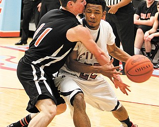 Fitch's Quincy Higgins (22) and John-Mark Weisman of Howland butt heads literally during the Division I sectional basketball game Tuesday at Alliance High School. The Falcons stunned the Tigers, 70-67, in overtime.