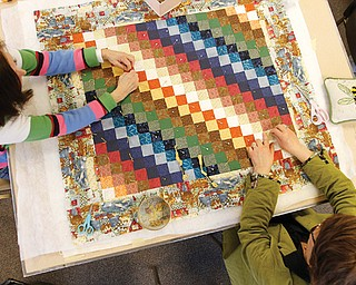 Linda Spencer, left, and Sherry Ziegler, members of Bethel Lutheran Church Piecemakers, work on a small-square rainbow colored quilt during a gathering Tuesday at the church in Boardman.