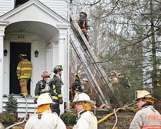 Firefighters work on a house fire at 323 S. Main Street in Poland on Thursday afternoon. The house, built in 1834, was being renovated at the time of the fire. Two dogs inside the home died, but homeowners were not in the house when the fire broke out.