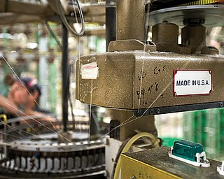 """A machine affixed with a """"Made in the U.S.A."""" plate is seen at the FesslerUSA apparel manufacturing plant in Orwigsburg, Pa. The U.S. economy grew at a 0.1 percent annual rate from October through December, the weakest performance in nearly two years, according to the Commerce Department's latest calculations, released Thursday. But economists believe a steady housing rebound and solid spending by consumers and businesses are pushing growth higher in the current quarter."""