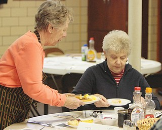 Sally Payne serves a made-to-order breakfast to June Barnes during the Lenten breakfast at Canfield Christian Church. The free meals include eggs, sausage and toast while pancakes and French toast are served on alternate weeks. Placemats feature a devotional.