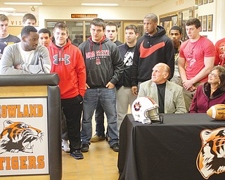 Longtime Mahoning Valley football coach Dick Angle, seated, announced his retirement Thursday at Howland High School. Michigan recruit De'Veon Smith, at podium, and other players saluted the Tigers' 15-year head coach.