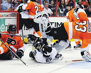Philadelphia Flyers' Scott Hartnell, left, and Pittsburgh Penguins' James Neal collide with goalie Brian Boucher and slide into the net during the third period of a game Thursday in Philadelphia. The Penguins won 5-4.