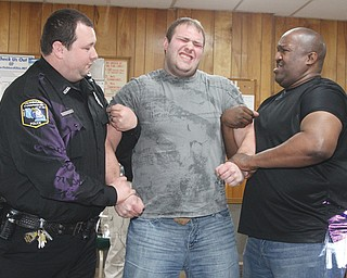 Hubbard Township Officer Justin Rydarowicz reacts to being shocked with a stun gun as fellow Officer Ken Steepleton, left, and Youngstown Officer Carlo Eggleston assist during police training Thursday night in Hubbard.