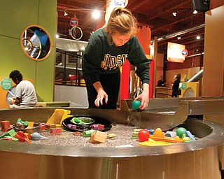 """Danielle Buseth, a freshman at North Dakota State University, spruced up the """"River of Knowledge"""" display at OH WOW! The Roger & Gloria Jones Children's Center for Science & Technology in Youngstown on Monday. Buseth was part of a group of 30 students traveling to Washington, D.C., and doing community-service projects along the way."""