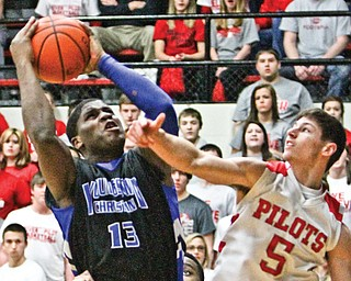 Youngstown Christian's Tymere Dubose (13) shoots over Hannibal River's Kameron Brown (5) during a Division IV regional semifinal Tuesday night at the Canton Memorial Fieldhouse. Youngstown Christian won, 60-49.