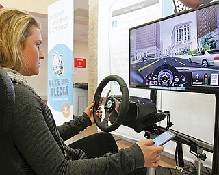 "Rachel Wyand, a senior at Canfield High School, goes through the texting and driving simulator during AT&T's ""It Can Wait"" program. The program, attended by local law enforcement and county officials, coincided with the enactment of Ohio's texting ban March 1."