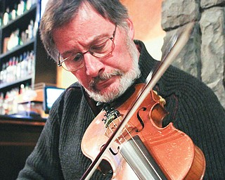 """Krygowski, of Poland, plays a tune on his fiddle. He also plays a six-holed woodwind instrument called a penny whistle. He says, """"Sharing tunes is just a beautiful social event."""""""