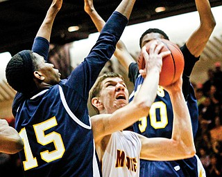 Cardinal Mooney's Doug Caputo (42) tries to shoot as he is hemmed in by Warrensville Heights defenders Jermaine Brown (15) and Trevon McGhee (30) during the Division II regional semifinal Thursday at Canton Memorial Fieldhouse. The Cardinals' season came to an end at the hands of the Tigers, who won 69-61.