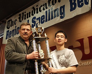 ROBERT  K.  YOSAY  | THE VINDICATOR --..Pronouncer Fred Owens PHD  - awards the Champion Trophy - to Max Lee - ..The 80th  Youngstown Vindicator Spelling Bee was held at Kilcawley Center on YSU Campus  Saturday morning with  60 competitors from area schools.. ..(AP Photo/The Vindicator, Robert K. Yosay)