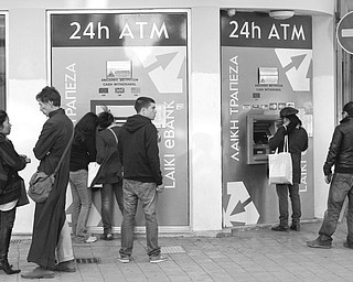 People wait to use the ATMs outside a Laiki Bank branch in Nicosia, Cyprus, on Sunday. Cyprus' president said he is trying to amend a bailout plan that would tax all bank deposits.
