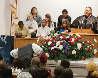 A mourner kisses the coffin of Daylan T. Ray, 15, after it was closed Monday as the Rev. Phillip Shealey of Greater Apostolic Faith Church in Warren delivers the eulogy. Daylan was one of six teens killed in a rollover SUV crash. The Rev. Mr. Shealey said parents have to be more vigilant as children grow.