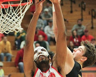 Youngstown State's Damian Eargle (21) goes to the basket as Oakland's Travis Bader (3) defends during a first-round CIT game Tuesday night at Beeghly Center. The Penguins won, 99-87.