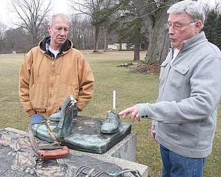 Clarence Huckaba , left, cemetery caretaker, and Gary Pollock, cemetery overseer, look over what is left of a 4-foot military statue that has been a fixture at Mahoning Valley Memorial Park for at least four decades. Thieves cut the statue off at the ankles and ran off with it. Below, Pollock looks over one of several pieces of the statue recovered from a scrap-metal dealer by police. Cemetery officials are hoping for swift justice.