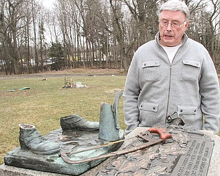 Gary Pollock, cemetery overseer at Mahoning Valley Memorial Park in Youngstown, looks over a monument where a military statue was sawed off with hacksaw last week. Police made an arrest in the theft Monday.