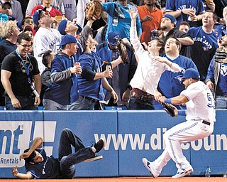 A fan falls onto the field as Toronto Blue Jays left fielder Melky Cabrera chases a foul ball during the fourth inning of the season opener against the Cleveland Indians on Tuesday in Toronto. The Indians won 4-1.