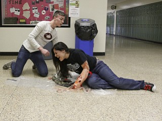 ROBERT K. YOSAY  | THE VINDICATOR..Juniors at BHS --  play the part of injured  student is Kaitlin McClendon  ( on the ground) as Cory Fowler comes to her aid..BPD and area law enforcement had a mock drill of a shooter at Boardman High School - .. - -30-..