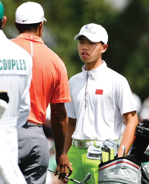 Golf prodigy Guan Tianlang, right, talks with Tiger Woods on the driving range during a practice round for the Masters on Monday in Augusta, Ga. The 14-year-old Tianlang of China is the youngest starter in U.S. Masters history.