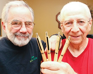 Austintown Fitch High School 1962 graduates Larry Cadman, left, and Jack Kidd display ink pens made of wood from the old Fitch High School gym floor. The pens are being used to raise money for a memorial to two Class of 1962 graduates who were killed in the Vietnam War.
