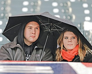 Fans sit under an umbrella in the rain at Progressive Field in Cleveland before the start of Thursday's baseball game between the Indians and Yankees Cleveland. The teams were rained out for the second night in a row.