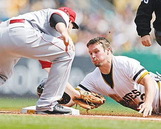 The Pirates' Travis Snider is tagged out by Reds third baseman Todd Frazier while attempting to steal third during the first inning of Sunday's game in Pittsburgh. Down 5-0 going into the seventh, the Pirates rallied to down the Reds, 10-7.
