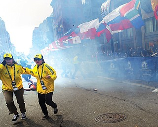 People react to an explosion at the Boston Marathon on Monday.