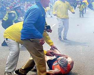 Volunteers react to a second explosion at the 2013 Boston Marathon on Monday. Medical personnel and public officials rushed to the aid of spectators, and the tent set up to care for fatigued runners was converted into a trauma clinic.