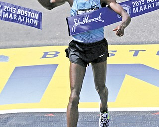 Lelisa Desisa of Ethiopia breaks the finish line tape to win the 2013 running of the Boston Marathon in Boston on