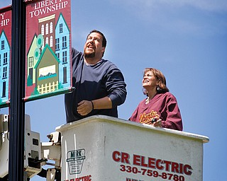 Top, Liberty Trustee Jason Rubin attaches a banner to a lamppost on Shady Road bridge Wednesday. The banners are a finishing touch on a bridge refurbishment project that began three years ago. Above, Rubin and Trustee Jodi Stoyak hoisted eight banners onto four lampposts throughout the day. Stoyak said the banners are meant to boost community pride as well as school spirit.